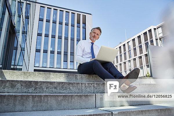 Portrait eines Geschäftsmannes auf einer Treppe mit Laptop