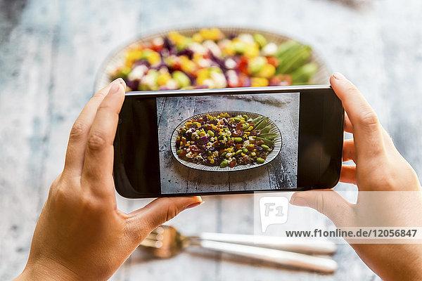 Mädchen fotografiert Quinoa-Salat mit Smartphone,  Nahaufnahme