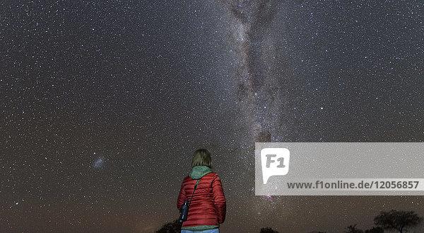 Namibia  Region Khomas  bei Uhlenhorst  Astrofoto  Sternenguckerin beim Beobachten des Kreuzes des Südens  eingebettet in die Milchstraße