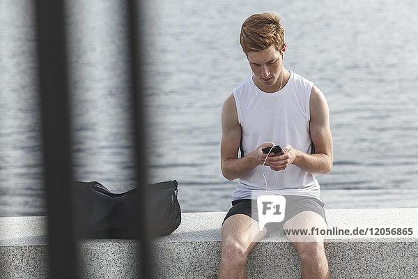 Junger Sportler an einer Wand am Flussufer mit Handy und Kopfhörer