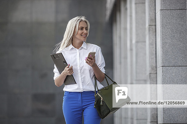 Lächelnde Geschäftsfrau mit Zwischenablage  Handtasche und Handy unterwegs