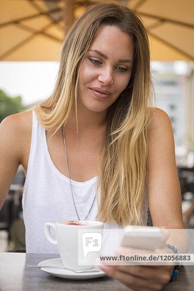 Junge Frau in einem Straßencafé  die ihr Handy überprüft.