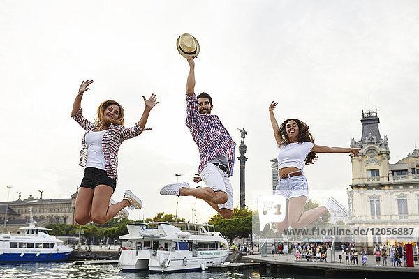 Spanien  Barcelona  drei Freunde beim Springen im Stadtzentrum am Meer