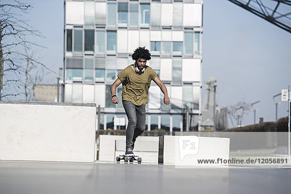 Young man riding longboard in skatepark