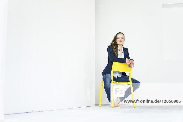 Geschäftsfrau auf einem gelben Stuhl sitzend  denkend