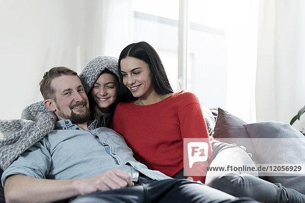 Eltern und Tochter kuscheln sich unter der Decke auf dem Sofa im Wohnzimmer.