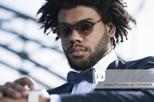 Serious young man with sunglasses looking at his smartwatch
