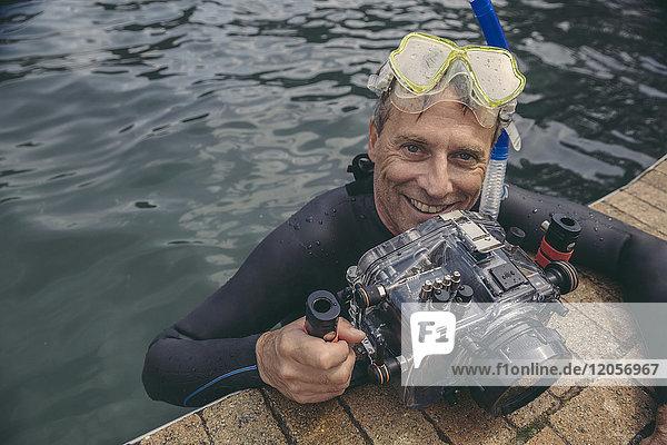 Porträt eines glücklichen Mannes mit Unterwasser-DSLR-Kameragehäuse im Wasser