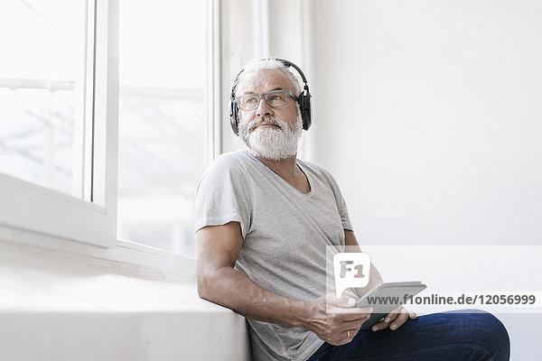 Erwachsener Mann mit Tablette und Kopfhörer aus dem Fenster schauend