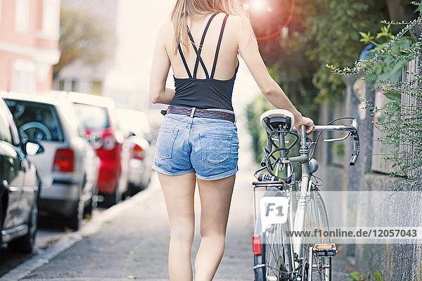 Junge Woan mit Fahrrad in der Stadt