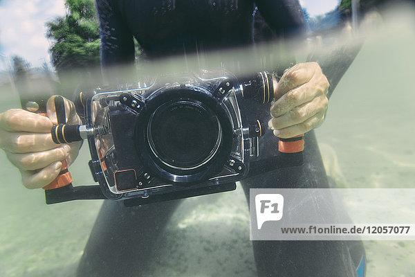 Mann mit Unterwasser-DSLR-Kameragehäuse in einem See