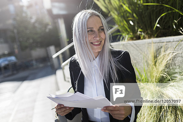 Smiling young businesswoman sitting on a wall in the city with documents