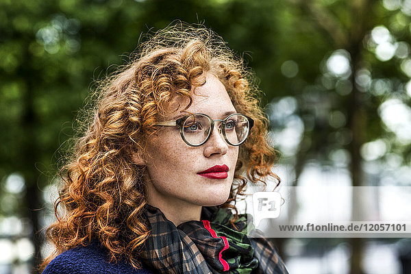 Portrait of redheaded young woman with red lips wearing glasses