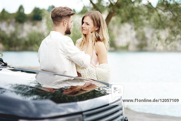 Liebevolles junges Paar außerhalb des Autos