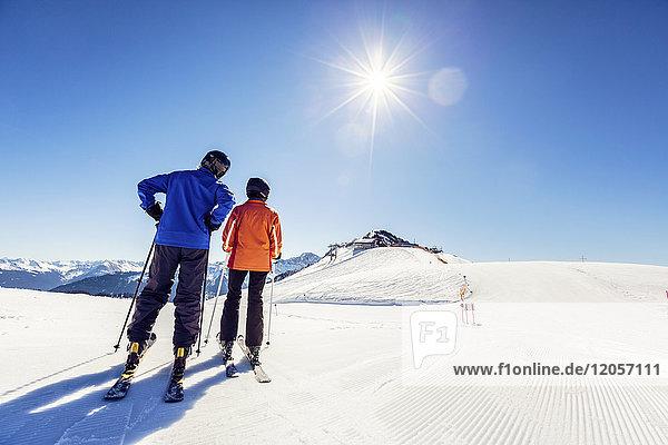 Österreich  Damuels  Paar mit Skifahrern in Winterlandschaft