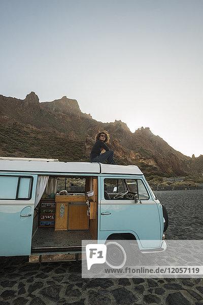 Spanien  Tenrife  Frau sitzend auf dem Dach eines Oldtimer-Vans