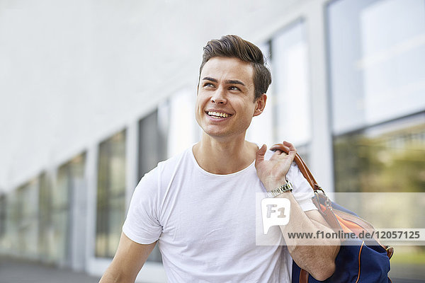 Porträt eines lachenden jungen Mannes mit Sporttasche