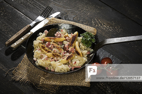 Bratpfanne aus fingerförmigen Kartoffelknödeln mit Sauerkraut und Speck auf Jute