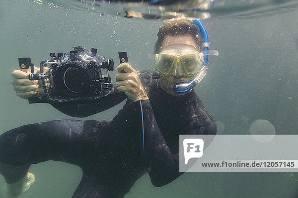 Mann taucht mit Unterwasser-DSLR-Kameragehäuse