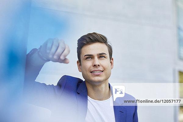 Porträt eines lächelnden jungen Mannes mit blauer Jacke