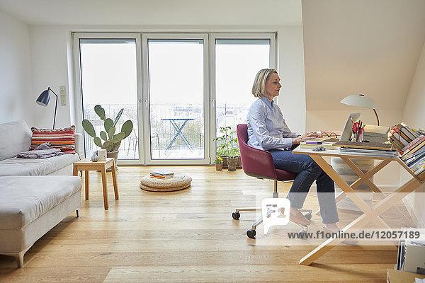 Reife Frau zu Hause mit Laptop am Schreibtisch