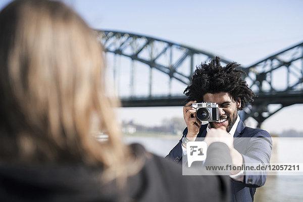 Lächelnder Mann im Anzug am Flussufer beim Fotografieren seiner Freundin mit einer alten Kamera