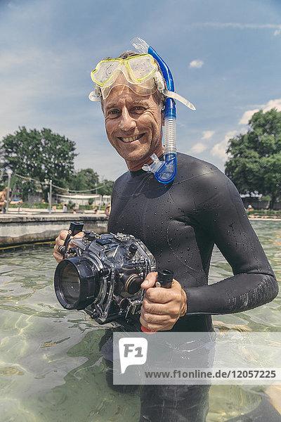 Porträt eines glücklichen Mannes mit Unterwasser-DSLR-Kameragehäuse im See
