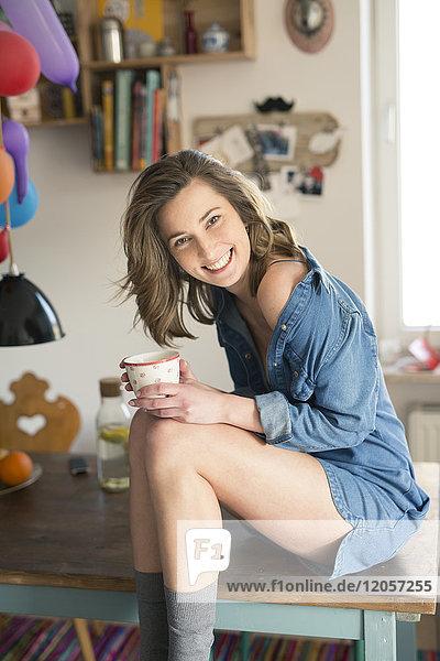 Porträt der lachenden Frau auf dem Küchentisch mit Kaffeetasse