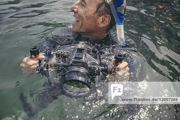 Glücklicher Mann mit Unterwasser-DSLR-Kameragehäuse im See