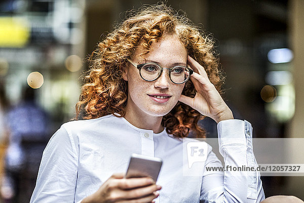 Portrait of smiling young woman with cell phone