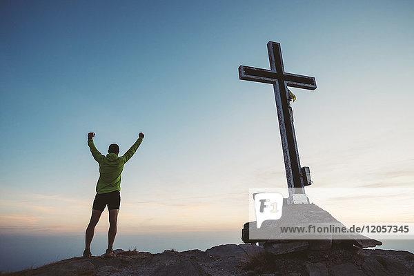 Italien  Bergläufer jubelt neben dem Gipfelkreuz