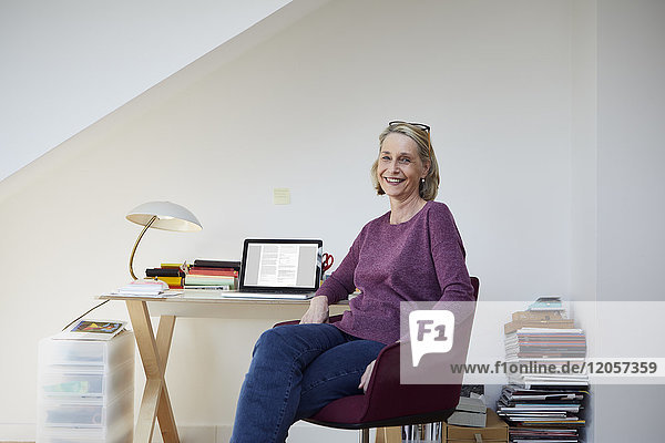 Portrait of smiling mature woman at home with laptop at desk