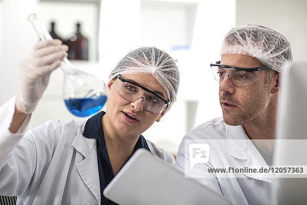 Zwei Wissenschaftler  die zusammen im Labor arbeiten und den Kolben untersuchen.