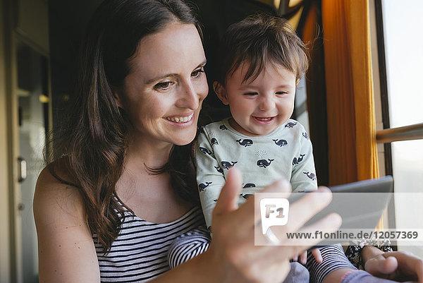 Glückliche Mutter und kleines Mädchen  die mit dem Smartphone unterwegs sind.