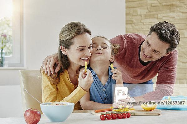 Glückliche Familie zu Hause bei der Zubereitung gesunder Speisen