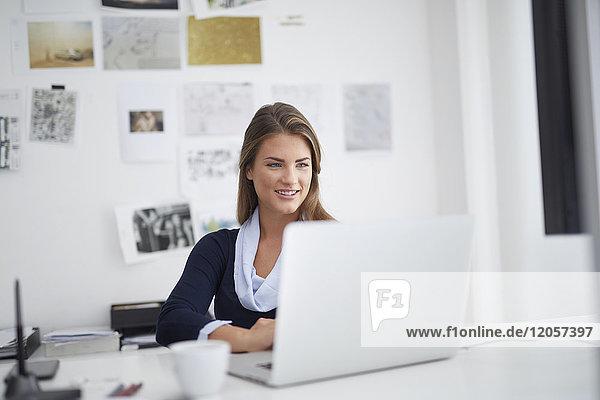 Lächelnde junge Frau mit Laptop am Schreibtisch im Büro