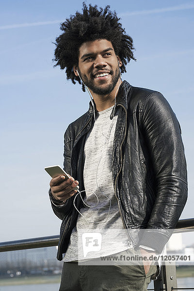 Smiling man with earphones listening to music on his smartphone