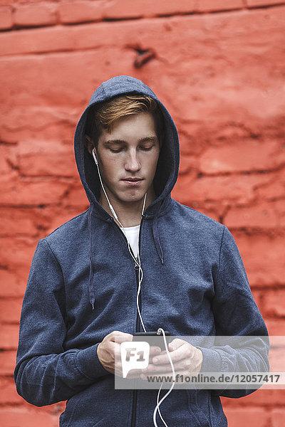 Junger Mann mit Handy und Kopfhörer an roter Ziegelwand