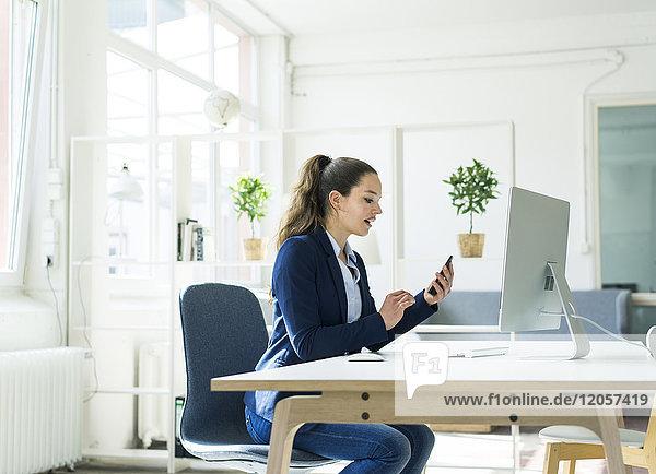 Geschäftsfrau am Schreibtisch prüft Handy