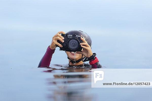 Lächelnde Frau mit Unterwasserkamera im Meer