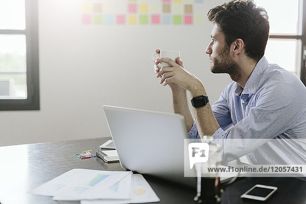 Young businessman working in office  drinking coffee