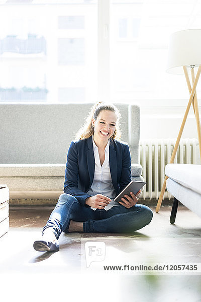 Smiling businesswoman sitting on floor using tablet