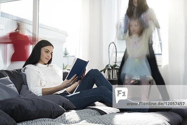 Mädchen springen auf dem Sofa  während die Mutter ein Buch liest.