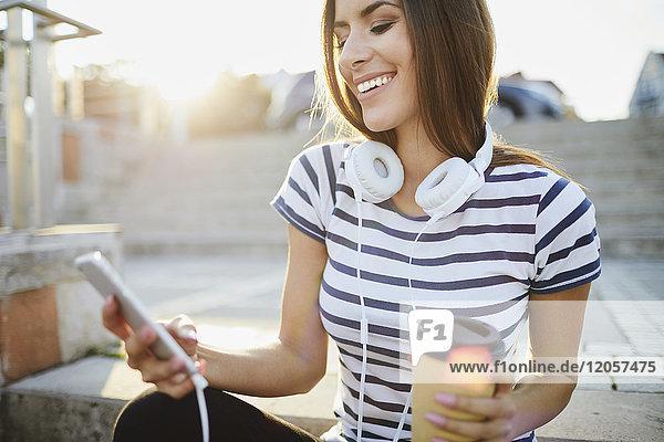 Frau mit Kopfhörer sitzt auf der Treppe in der Stadt mit Smartphone und Kaffee