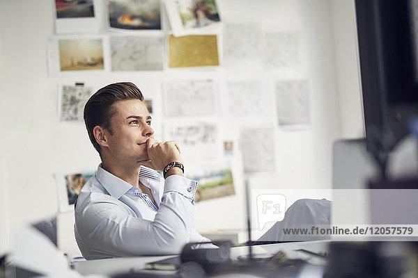 Porträt eines nachdenklichen jungen Geschäftsmannes  der am Schreibtisch im Büro sitzt.