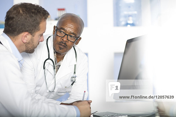 Two doctors discussing at computer screen