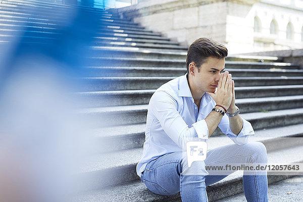 Nachdenklicher junger Mann auf der Treppe sitzend