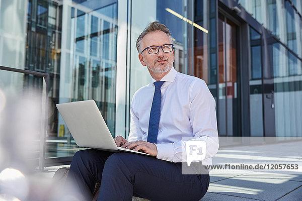 Portrait eines Geschäftsmannes mit Laptop im Freien