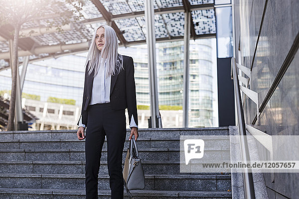 Young businesswoman standing on stairs in the city