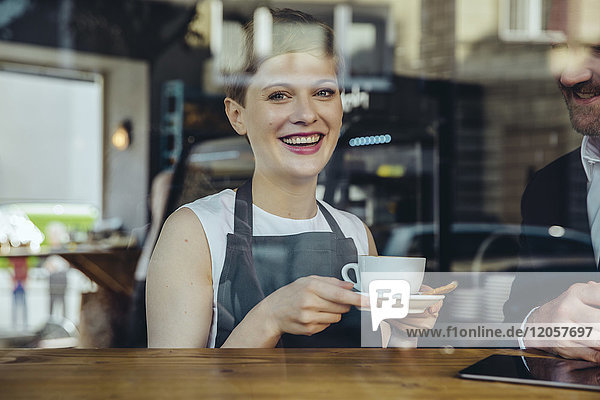Lächelnde Kellnerin serviert dem Kunden Kaffee im Cafe